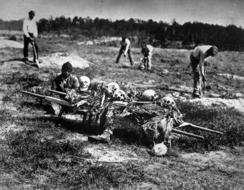 Man sitting down near cart full of skeletal remains of soldiers as black laborers dig graves in background on Civil War battlefield. Cold Harbor, VA, April 1865 Photographer: John Reekie