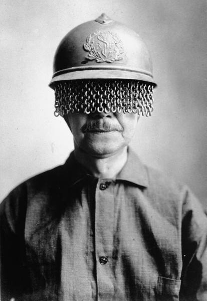 Mustachioed man wearing steel helmet w. built-on chain screen to protect soldiers' eyes from fragments of shell, rock, etc. during WWI; manufactured by E.J. Codd Co., Baltimore, MD, 1918